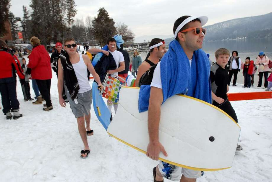 Nick Barone of Averill Park, right, leads his surfer friends, including Tom Probst, left, and Tom Cooley, center, to the beach Friday for the annual Lake George Winter Carnival's First Day Polar Plunge in Lake George Village. (Cindy Schultz / Times Union) Photo: CINDY SCHULTZ