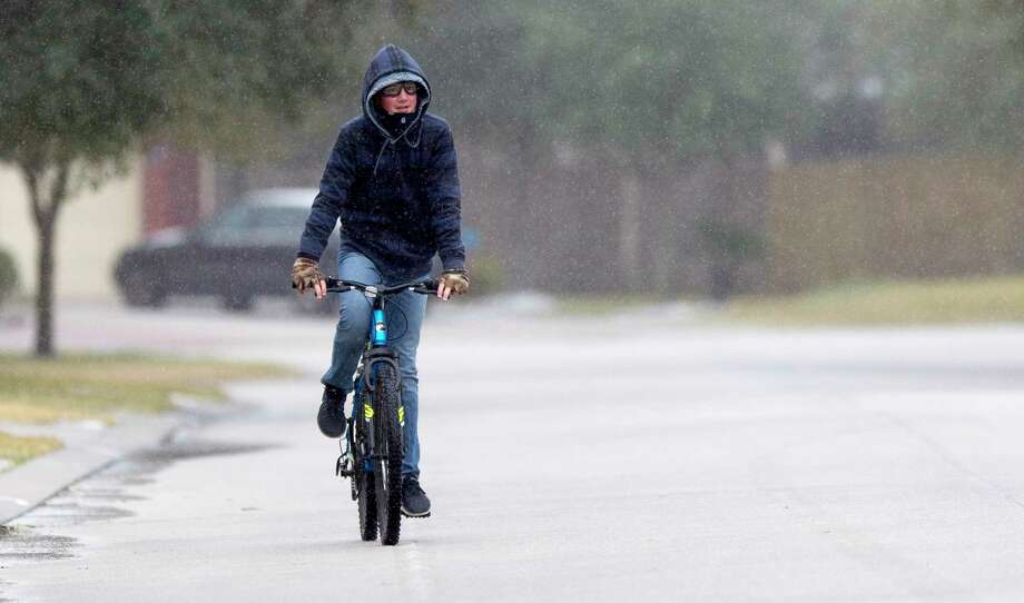 William Johnson, 14, rides his bike as sleet rains down after a winter storm brought freezing rain and ice throughout the greater Houston area, Tuesday, Jan. 16, 2018. The National Weather Service issued a Winter Storm Warning for southeast Texas until midnight Wednesday. Photo: Jason Fochtman, Staff Photographer / © 2018 Houston Chronicle