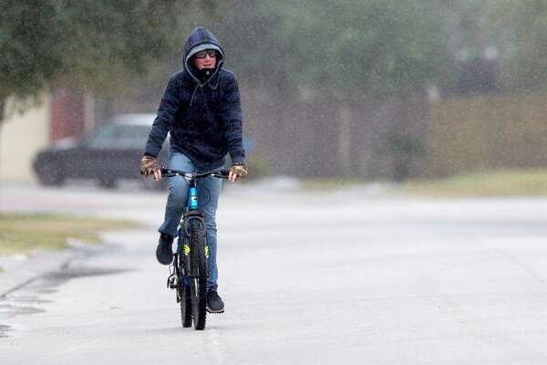 William Johnson, 14, rides his bike as sleet rains down after a winter storm brought freezing rain and ice throughout the greater Houston area, Tuesday, Jan. 16, 2018. The National Weather Service issued a Winter Storm Warning for southeast Texas until midnight Wednesday.