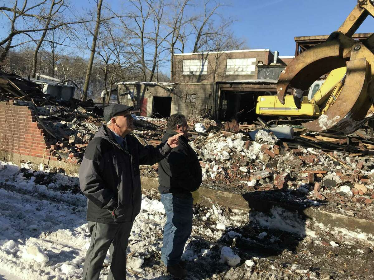 Carmen DiCenso, Derby's economic development liaison, confers with Frank Pepe, owner of F.Pepe Construction during the Jan. 10 demolition of a building at 150 Roosevelt Drive.