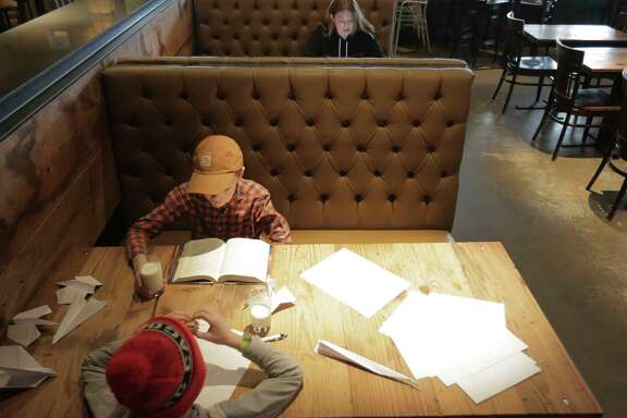 Jordann Foreman, from right, works while her sons, Seamus, 9, and Miles, 6, occupy themselves in a booth at The Hay Merchant on  Tuesday, Jan. 16, 2018, in Houston. Foreman, an events manager with Underbelly, had to take her children to work with her because of the school closing. ( Elizabeth Conley / Houston Chronicle )
