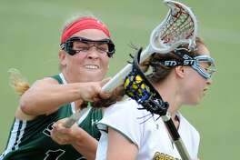 Ryan Smith, left, of Sacred Heart, goes for the stick-check as Greenwich Academy's Tessa Brooks advances the ball during the high school lacrosse match between Sacred Heart Greenwich and Greenwich Academy at Sacred Heart, Greenwich, Conn., Saturday, April 29, 2017. GA defeated Sacred Heart 11-8.