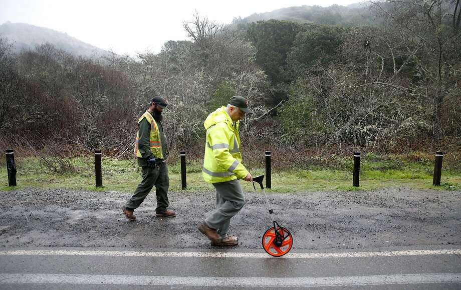 Danny Dixon (left) and Jim Fusscas take measurements for placing barricades to prevent roadside parking on Frank Valley Road. Photo: Paul Chinn, The Chronicle