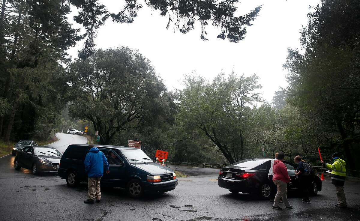 Visitors get out of their cars at the main entrance before drivers head for parking lots on the first day of a reserved parking system at Muir Woods National Monument in Mill Valley, Calif. on Tuesday, Jan. 16, 2018.