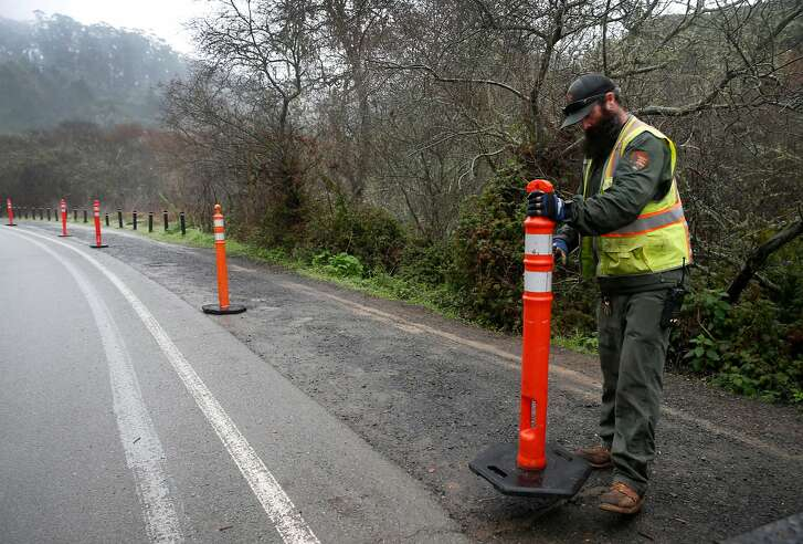 Danny Dixon places temporary barricades to restrict parking along Franks Valley Road on the first day of a reserved parking system at Muir Woods National Monument in Mill Valley, Calif. on Tuesday, Jan. 16, 2018.