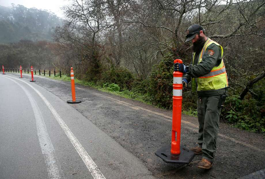 Danny Dixon places temporary barricades to prevent parking along Frank Valley Road on the first day of a reserved parking system at Muir Woods National Monument in Mill Valley. Photo: Paul Chinn, The Chronicle