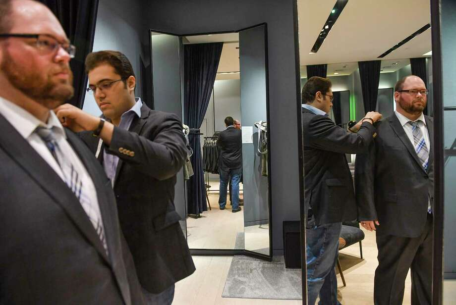 Kiavash Asghari, center, measures customer Bobby Bartlett for a new suit at Indochino in McLean, Va. Photo: Washington Post Photo By Ricky Carioti / The Washington Post