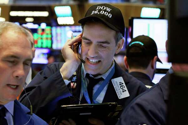 """Trader Gregory Rowe, center, wears a """"Dow 26,000"""" hat as he works on the floor of the New York Stock Exchange, Tuesday, Jan. 16, 2018. The Dow Jones industrial average traded above 26,000 for the first time. (AP Photo/Richard Drew)"""