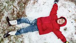 Zach Arnold tries to make a snow angel while playing in the snow on Tuesday in Spring. Unusually low temperatures and a mix of precipitation brought the Houston area to a standstill Tuesday.