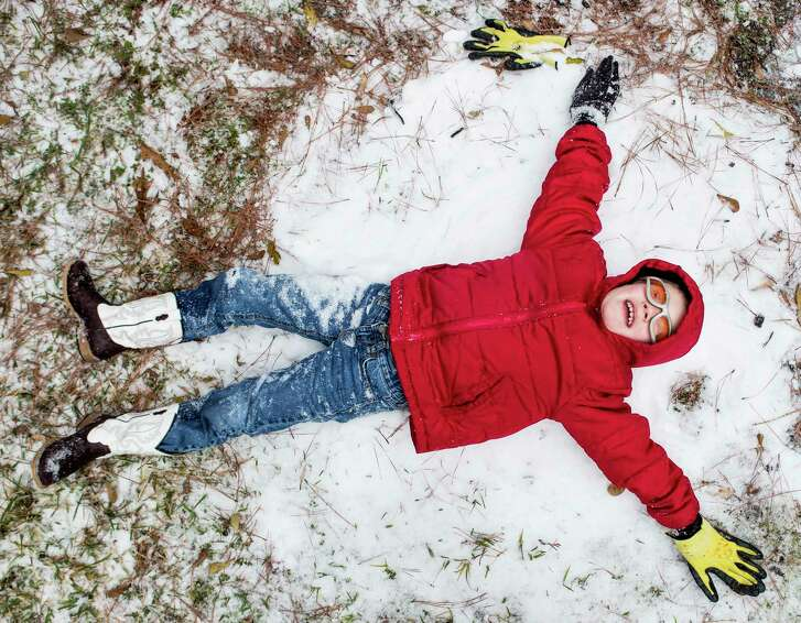 Zach Arnold tries to make a snow angel while playing in the snow on Tuesday, Jan. 16, 2018, in Spring. ( Brett Coomer / Houston Chronicle )
