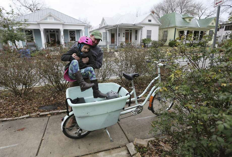 Pastor John Garland of San Antonio Mennonite Church lifts his daughter, Aurora, into a bike carrier as he goes to harvest vegetables at the church garden on Tuesday, Jan. 16, 2018. Since schools were closed due to the icy weather, Aurora was able to spend time accompanying her father as he prepared the vegetables to sell to a nearby restaurant. (Kin Man Hui/San Antonio Express-News) Photo: Kin Man Hui, Staff / San Antonio Express-News / ©2018 San Antonio Express-News
