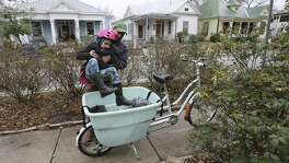 Pastor John Garland of San Antonio Mennonite Church lifts his daughter, Aurora, into a bike carrier as he goes to harvest vegetables at the church garden on Tuesday, Jan. 16, 2018. Since schools were closed due to the icy weather, Aurora was able to spend time accompanying her father as he prepared the vegetables to sell to a nearby restaurant. (Kin Man Hui/San Antonio Express-News)