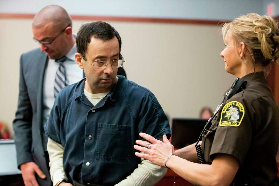 Former USA Gymnastics doctor Larry Nassar is about to be led away following his sentencing hearing in Lansing, Michigan, January 16, 2018. Victims of sexual abuse by Nassar delivered gut-wrenching emotional testimony at the court hearing which could see him sentenced to prison for life. Nassar has been accused of molesting more than 100 female athletes during the three decades he worked with USA Gymnastics and at Michigan State University. Photo: GEOFF ROBINS / AFP or licensors