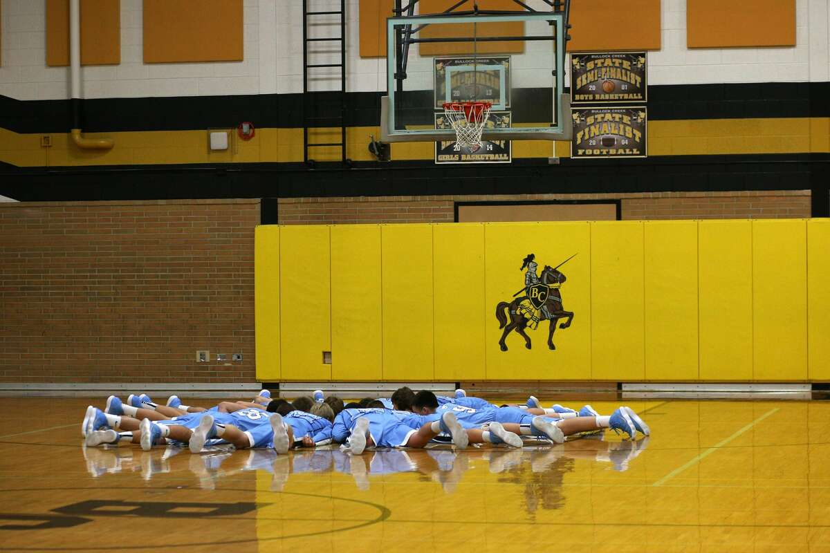 Meridian players lay on the ground before the game against Bullock Creek at Bullock Creek High School on Tuesday, Jan. 16, 2018. (Samantha Madar/for the Midland Daily News)