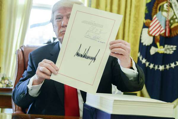 President Donald Trump holds the tax overhaul bill after signing it into law in the Oval Office last month.