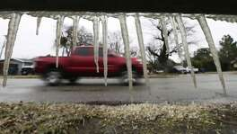 Icicles hang from a bus stop bench as a motorist ventures along Vance Jackson Road on Tuesday, Jan. 16, 2018. An overnight blast of Arctic air combined with precipitation shuttered most of the city on Tuesday. Motorists who ventured out encountered numerous accidents along the roads and icy overpasses. (Kin Man Hui/San Antonio Express-News)