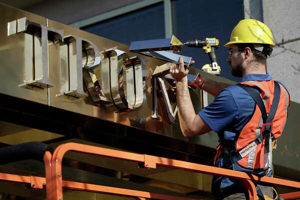 "A worker removes the words ""Trump Place"" from a residential building Nov. 16, 2016, in New York Nov. 16, 2016."