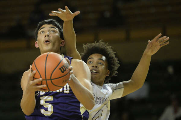 Midland High's Nat Rodriguez (5) tries to lay up against Lee's Cevonte Eaden (4) Jan. 16, 2018, at Chaparral Center.  James Durbin/Reporter-Telegram