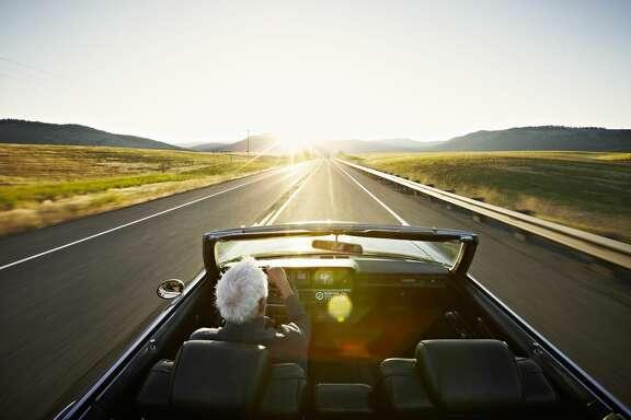 Senior man driving convertible car at sunrise on rural highway