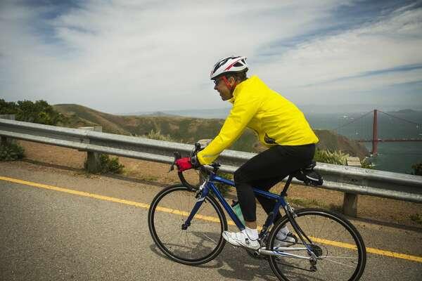 Hispanic man riding bicycle on waterfront road