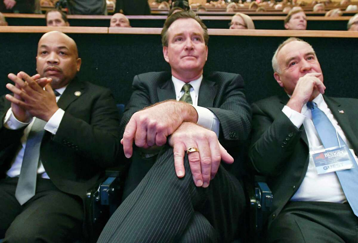 Assembly Speaker Carl Heastie, D-Bronx, left, Senate Majority Leader John Flanagan, R-Smithtown, center, and Thomas P. DiNapoli state Comptroller, right, listen to New York Gov. Andrew Cuomo deliver his 2018 executive state budget proposal during a news conference at the Clark Auditorium in Albany, N.Y., Tuesday, Jan. 16, 2018. (AP Photo/Hans Pennink)
