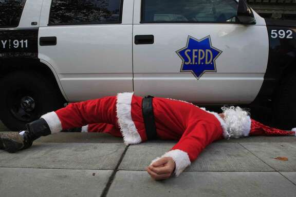 A man dressed as Santa Claus lies next to a San Francisco Police car after Santa Con patrons were pushed out of Union Square in preparation for a possible protest during the 20th Annual Santa Con in San Francisco, Calif. Saturday, December 13, 2014.