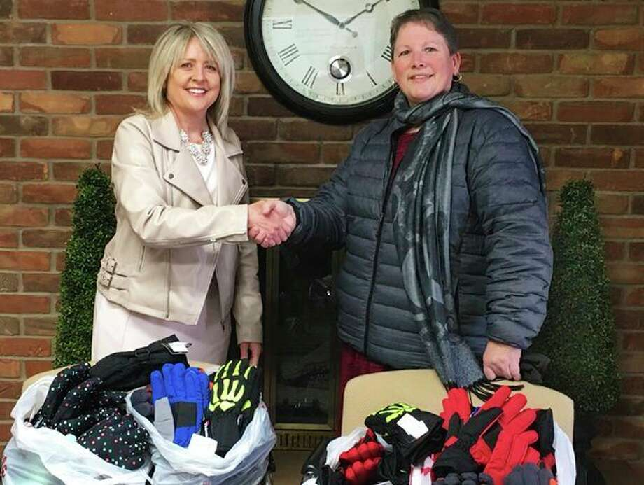 Beaverton Rural Schools Superintendent Susan Wooden, left, accepts 125 new pairs of gloves and mittens from Dow Chemical Employees' Credit Union Executive Assistant to the CEO Susan Phillips. On behalf of the Midland‑based credit union, Phillips delivered the cold‑weather gear for distribution to students at Beaverton Elementary School during the week of Jan. 1, when local temperatures and wind chills were dipping to subzero levels.