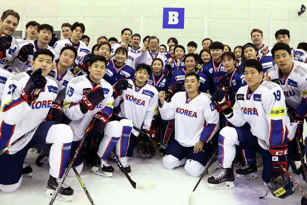 South Korean President Moon Jae-in, center top, poses with South Korean women's and men's ice hockey team players during a visit to Jincheon National Training Center in Jincheon, South Korea, Wednesday, Jan. 17, 2018. There is growing concern in South Korea that a proposal to form a joint women's hockey team with North Korea for the Olympics could be bad for the South Korean players. (Ha Sa-hun/Yonhap via AP)