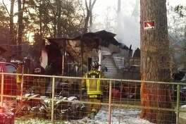 Officials surround a burned mobile home fire off of Cherry Laurel Street in Huffman, Texas on Jan. 17, 2018. A mother and her three children died in the blaze, Harris County Sheriff Ed Gonzales said.