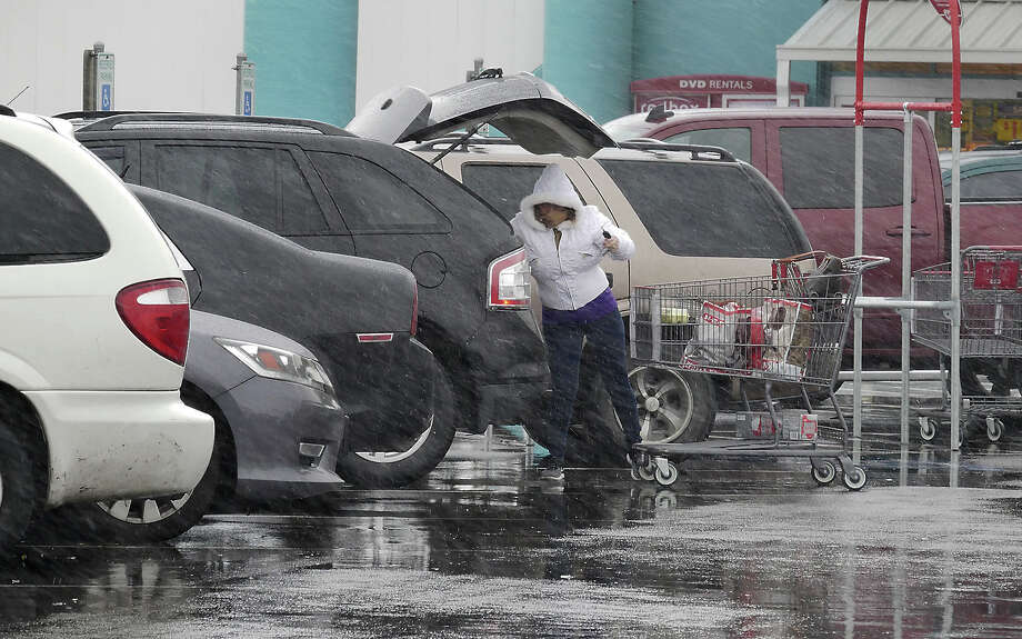 A shopper at the HEB Store on San Dario Avenue and Calton Road loads her groceries into her vehicle as freezing rain falls, Tuesday, January 16, 2018. Photo: Cuate Santos, Laredo Morning Times / Laredo Morning Times