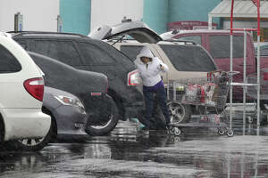A shopper at the HEB Store on San Dario Avenue and Calton Road loads her groceries into her vehicle as freezing rain falls, Tuesday, January 16, 2018.