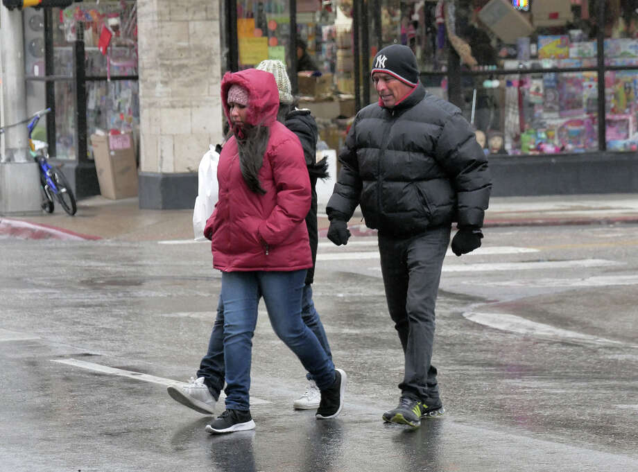 Shoppers are bundled against the cold and wet weather as they cross Convent Avenue Tuesday, January 16, 2018. Photo: Cuate Santos, Laredo Morning Times / Laredo Morning Times