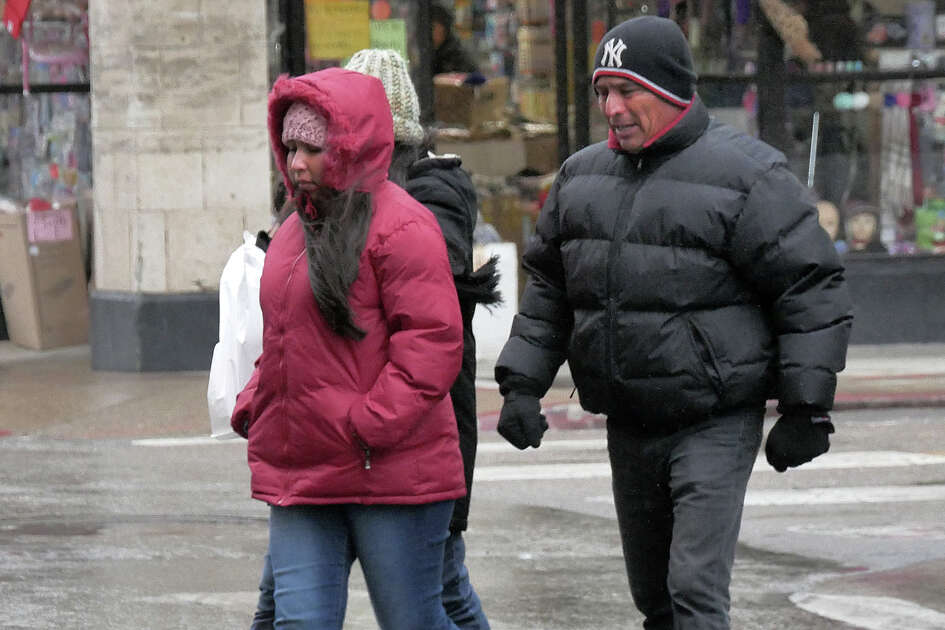 Shoppers are bundled against the cold and wet weather as they cross Convent Avenue Tuesday, January 16, 2018.