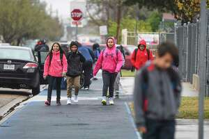 Students from Santa Maria Elementary School bundle up as classes let out early on Tuesday, Jan. 16, 2018, as a strong cold front brings near freezing temperatures to South Texas.