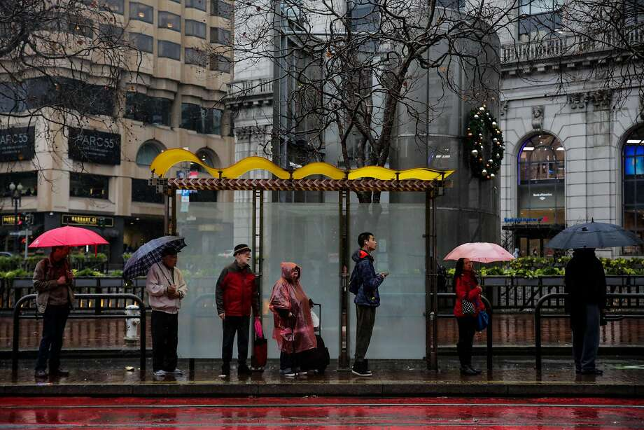 A light rain shower will begin just after midnight in the Bay Area bringing scattered showers through Friday and colder temperatures, forecasters said. People wait for the bus in the rain on Market Street in San Francisco, Calif., on Monday, Jan. 8, 2018. Photo: Gabrielle Lurie, The Chronicle