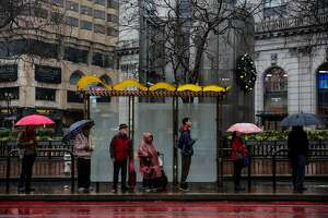 People wait for the bus in the rain on Market Street in San Francisco, Calif., on Monday, Jan. 8, 2018.