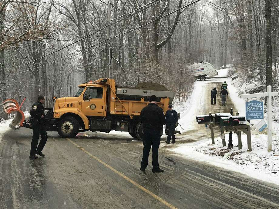 A garbage truck driver was injured when he was hit as he tried to jump out of  his truck after it slid out of control on a steep private driveway off Nashville Road in Bethel. Photo: Zach Murdock / Hearst Connecticut Media