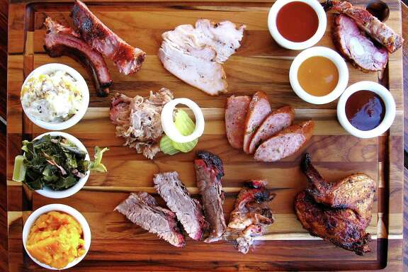 Meat and sides from Big Bib BBQ. Clockwise from bottom left: sweet potato casserole, collard greens, baked potato casserole, babyback ribs, smoked turkey, Bib Sauce, Tangy Gold sauce, Hot N' Spicy sauce, rib tips, smoked chicken, brisket, pulled pork and jalapeño sausage.
