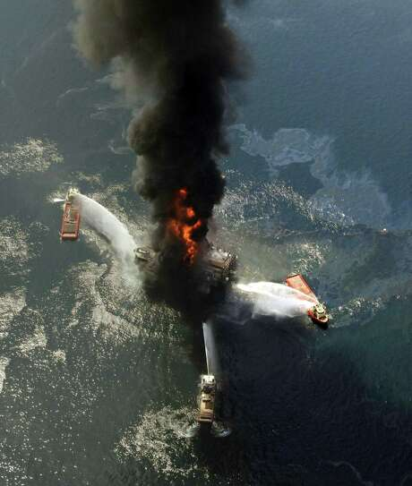FILE - In an April 21, 2010 file photo, the Deepwater Horizon oil rig burns after a deadly explosion in the Gulf of Mexico. The 2010 explosion at a well in the Gulf of Mexico threatened BP's existence after 11 people were killed and millions of barrels of oil spilled into the sea. The London-based company said it's recording a new $1.7 billion charge in the fourth quarter of 2017 and pay $1 billion of that bill in 2018. Photo: Gerald Herbert /Associated Press / AP