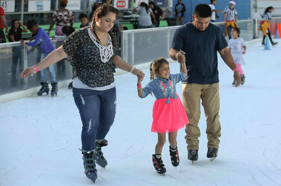 Josue and Tiffany Sermeno hold hands with their daughter, Aolanie, 6, to navigate in the ice rink at Discovery Green on Sunday, Nov. 26, 2017, in Houston. Photo: Yi-Chin Lee, Houston Chronicle / © 2017  Houston Chronicle