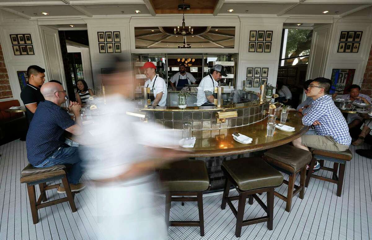 Diners enjoy happy hour, featuring $1 oysters, at the oyster bar at State Of Grace in River Oaks.