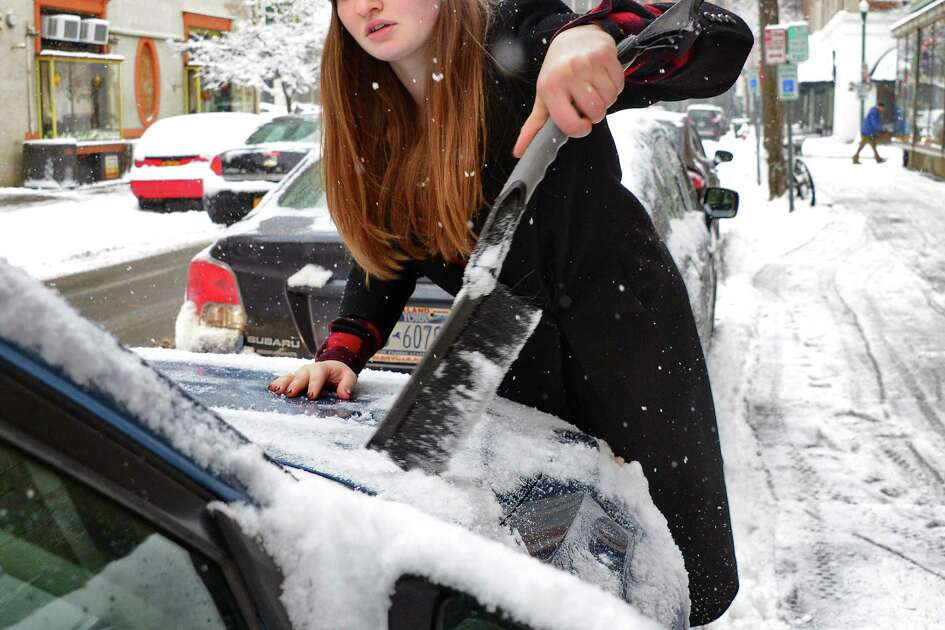Megan Moran clears snow from her car on her way to work Wednesday Jan. 17, 2018 in Troy, NY.  (John Carl D'Annibale/Times Union)