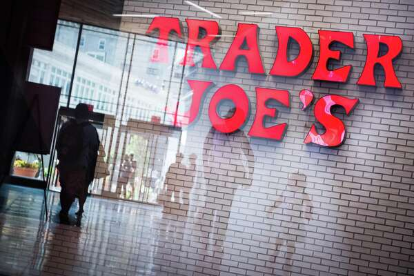 Shoppers are reflected in a window in front of Trader Joe's grocery store signage in the Brooklyn borough of New York on July 18, 2017.