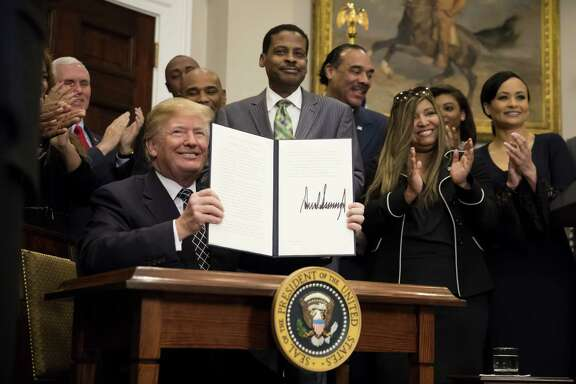 President Donald Trump holds up a signed proclamation for Martin Luther King Jr. Day in the Roosevelt Room of the White House on Jan. 12, 2018.  (Eric Thayer / Bloomberg)