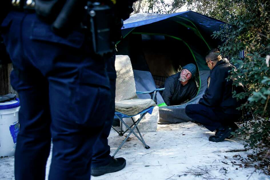 Harris County Sheriffs Homeless Outreach Team member Luke Ditta, right, checks in on Charles Lundquist, who spent the night in his tent off Grant Road and Tomball Parkway, as freezing weather passes through the region Wednesday, Jan. 17, 2018 in Houston.