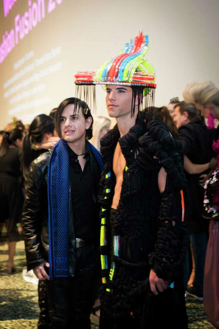 A guest posing for a photo next to a model wearing a creation by Kyndall Bollmeyer at Fashion Fusion, Thursday, Jan. 11, 2018, in Houston.