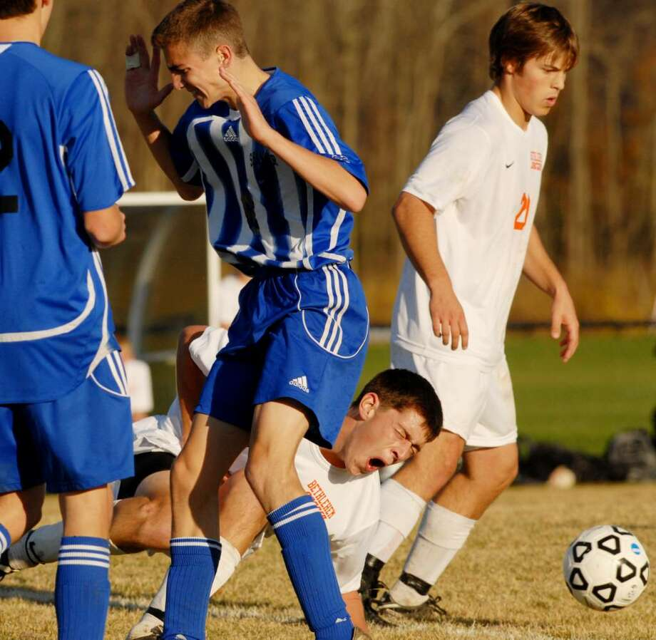 Shaker's Austin Britt, center, has just collided with No. 23 Bethlehem's Dan Krzykowski, (on the ground) in Class AA boys' soccer quarterfinal action at Bethlehem High School. (Luanne M. Ferris / Times Union) Photo: LUANNE M. FERRIS / 00006208A