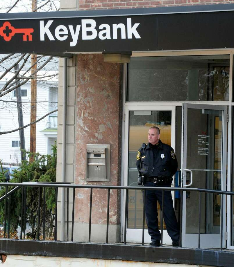 Albany police officer Robert Poole stands guard on the front door of the KeyBank at 3 Colvin Ave. after it was robbed by a man who fled with an unknown amount of money. (Skip Dickstein / Times Union) Photo: SKIP DICKSTEIN