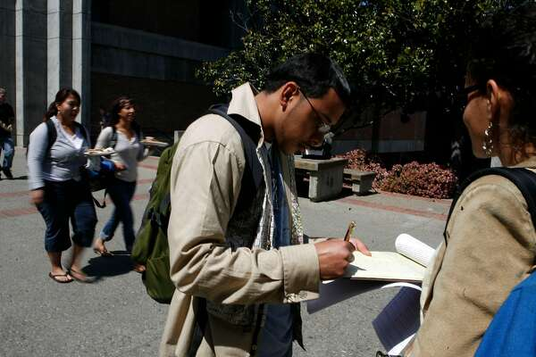 Christopher Timbo` Temblador (left) signs a petition that  Christina Roehl (right) was having people sign on campus at San Jose State University on Monday April 14, 2008 in San Jose, Calif. The voter registration group Voto Latino is teaming up with the Hispanic-oriented English-language entertainment network S�TV to embed two youthful Latinos as reporters covering the Democratic and Republican conventions this summer. Christopher Timbo`  Temblador hopes to be embeded at the Democratic National Convention. .Photo By Lea Suzuki/ San Francisco Chronicle