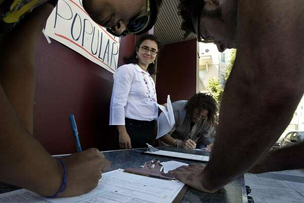 LATINO021_kw.JPG Mission residents Francine Madrid (Left), Saner (CQ) Cotte (BACKGROUND),  and Tim Lilly  (RIGHT) fill out their registration forms with encouragement from  Renee (CQ)Saucedo (CQ) (CENTER). Saucedo (CQ) (CENTER white shirt), program coordinator at La Raza Centro Legal,  a Latino political leader has geared up her efforts to get latino voters registered  and out to the polls for the October 7th recall election by setting up a table in front of their Mission District office on 8/12/03 in San Francisco.     KAT WADE / The Chronicle